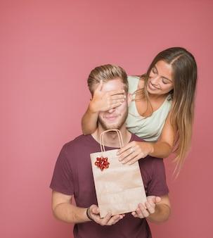 Giovane donna che copre i suoi occhi ragazzo mentre dando regalo a lui