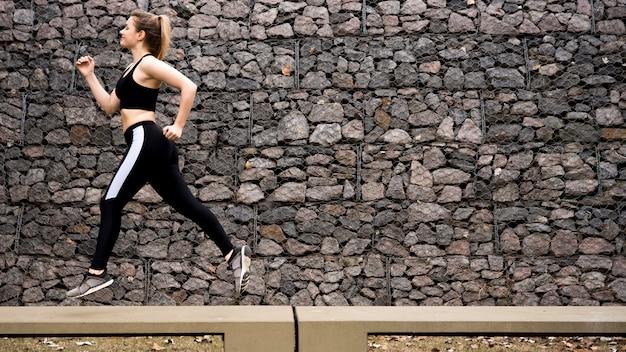 Giovane donna che corre all'aperto con abiti sportivi