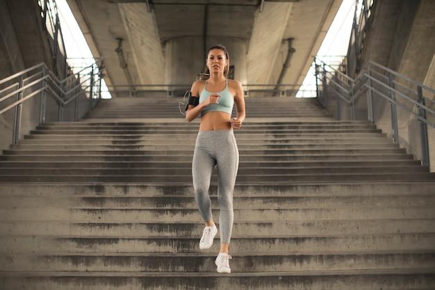 Giovane donna che corre da solo giù per le scale all'aperto nell'ambiente urbano