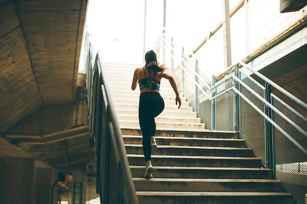 Giovane donna che corre da solo su per le scale