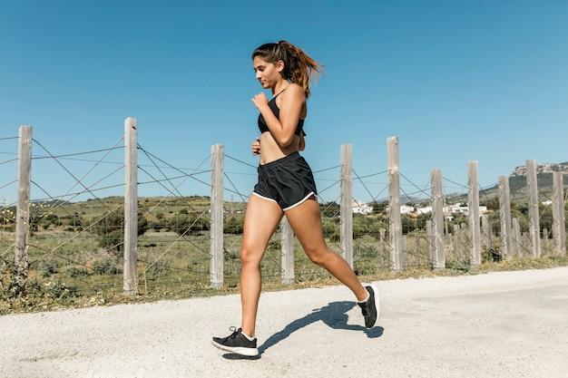 Giovane donna che corre lungo la strada di campagna