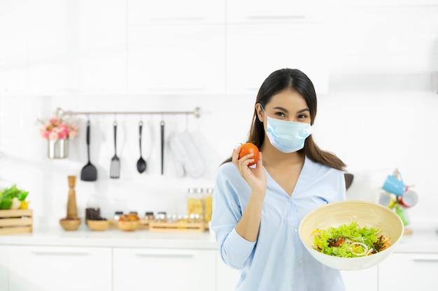Giovane donna che cucina cibo delizioso in cucina e indossa una maschera di protezione per il viso contro la saliva, tosse. resta a casa durante l'auto-quarantena covid-19 14 giorni.