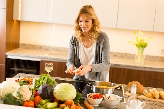 Giovane donna che cucina cibo sano nella cucina moderna