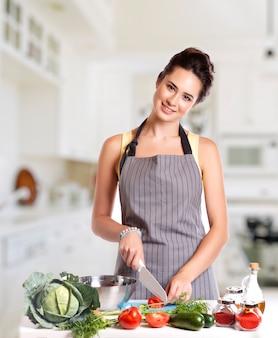 Giovane donna che cucina in cucina.