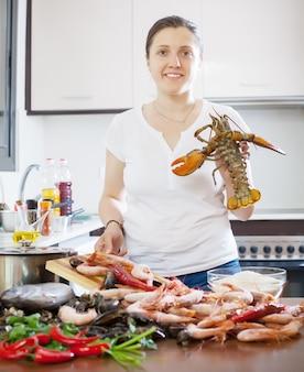 Giovane donna che cucina prodotti marini