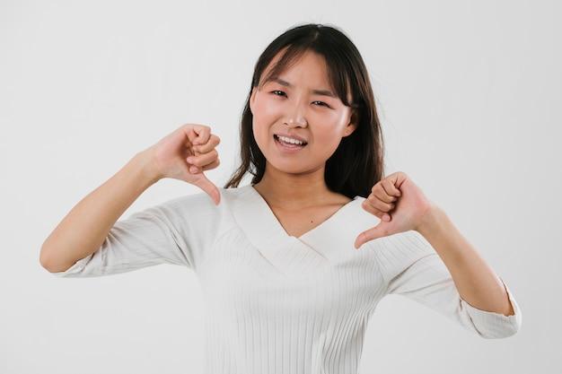 Giovane donna che dà il segno di antipatia