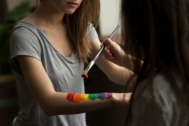 Giovane donna che dipinge la bandiera arcobaleno sulla mano della sua ragazza con il pennello