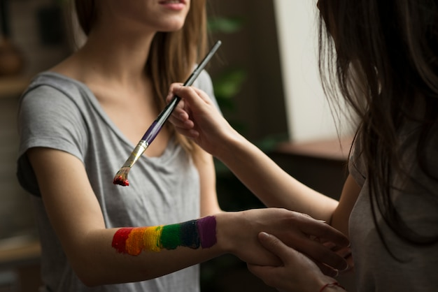 Giovane donna che dipinge la bandiera arcobaleno sulla mano della sua ragazza