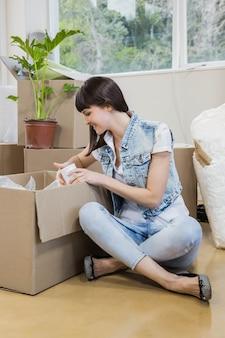 Giovane donna che disimballa i contenitori di cartone in nuova casa