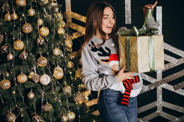 Giovane donna che disimballa regalo di natale dall'albero di natale
