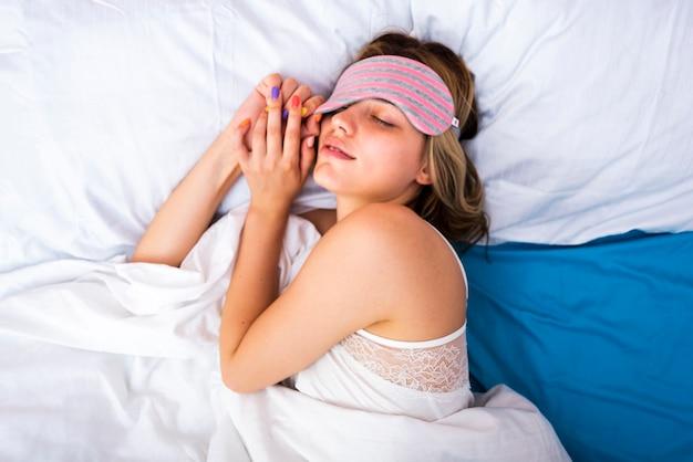 Giovane donna che dorme nel letto