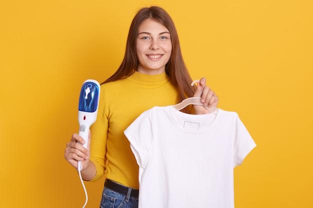 Giovane donna che è pronta a cuocere a vapore i suoi vestiti sullo scaffale a casa, preparando per uscire, indossando la camicia casual gialla