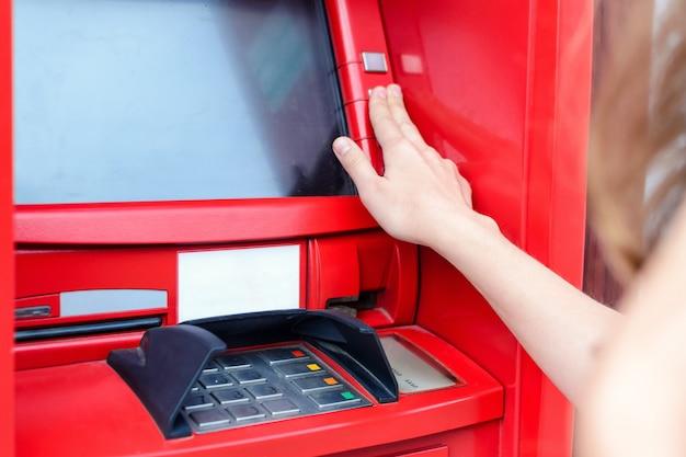 Giovane donna che effettua il pagamento al bancomat