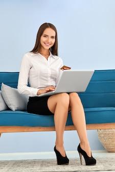 Giovane donna che effettua pagamento online che si siede sul sofà