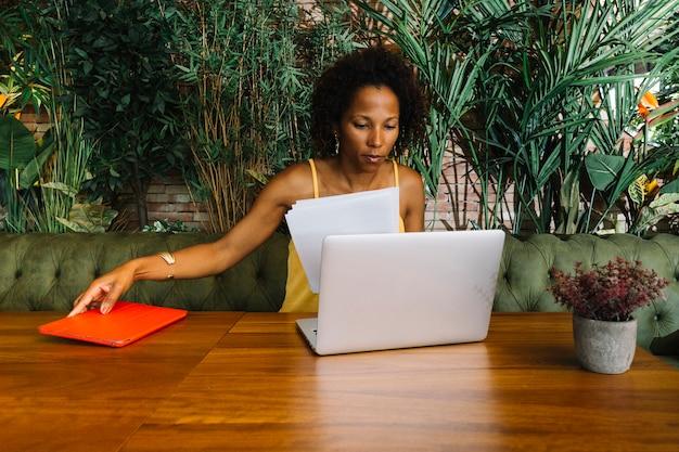 Giovane donna che esamina documento della tenuta del computer portatile e compressa digitale sulla tavola di legno