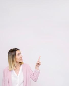 Giovane donna che esamina il contesto vuoto bianco che indica verso l'alto