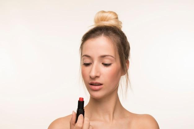 Giovane donna che esamina rossetto
