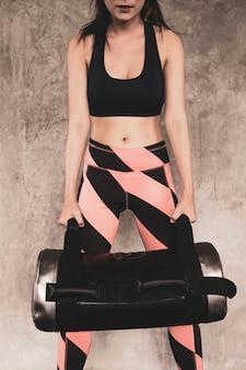 Giovane donna che esercita la costruzione di muscoli in palestra