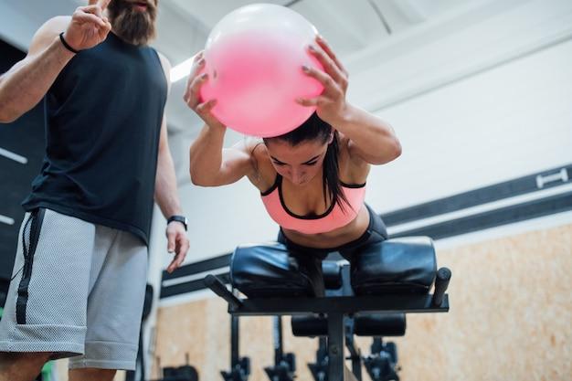 Giovane donna che esercita palestra coperta con personal trainer