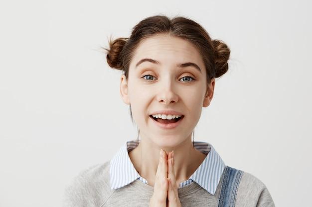 Giovane donna che esprime positività e felicità che stanno insieme con le palme sopra la parete bianca. ragazza candida castana che chiede ai suoi genitori di andare al campeggio estivo che gesturing con le mani. avvicinamento