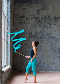 Giovane donna che fa ballo relativo alla ginnastica con il nastro blu