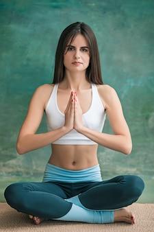 Giovane donna che fa esercizi di yoga sulla parete verde