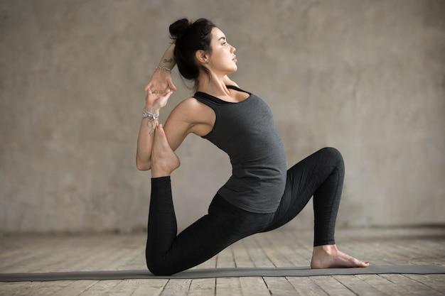 Giovane donna che fa esercizio anjaneyasana