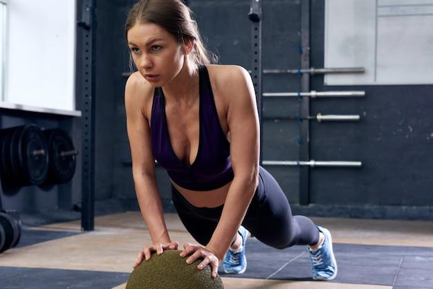 Giovane donna che fa esercizio della plancia sulla palla