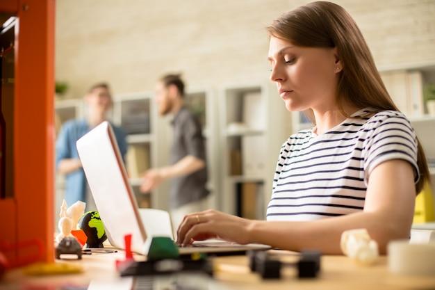 Giovane donna che fa funzionare la stampante 3d