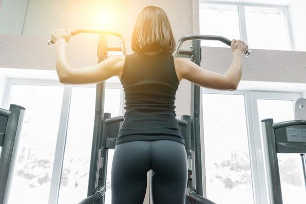 Giovane donna che fa gli esercizi per la parte posteriore sulla macchina di forma fisica in palestra