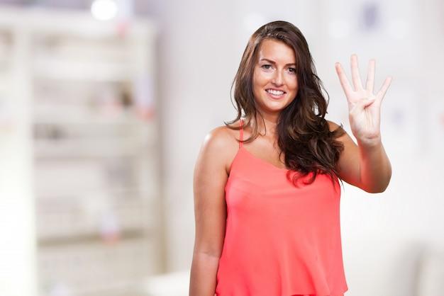 Giovane donna che fa il numero quattro