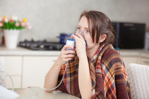 Giovane donna che fa inalazione con un nebulizzatore a casa