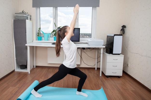 Giovane donna che fa le esercitazioni a casa
