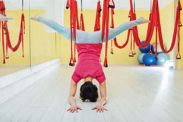 Giovane donna che fa le esercitazioni antigravità di yoga