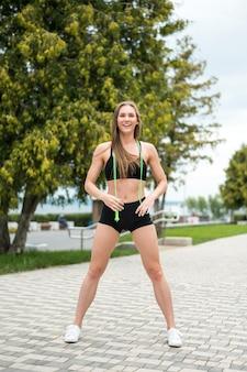 Giovane donna che fa le esercitazioni con il salto della corda