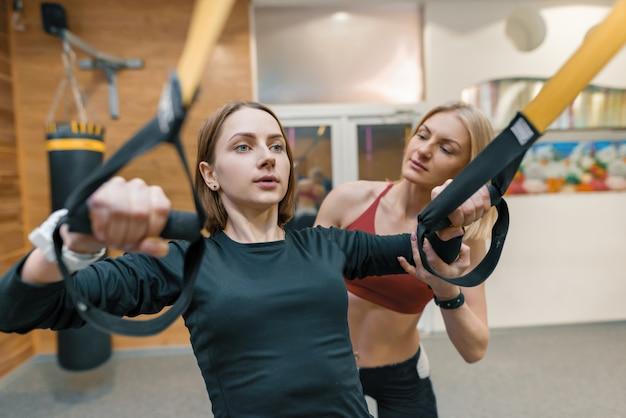 Giovane donna che fa le esercitazioni con l'istruttore personale di forma fisica