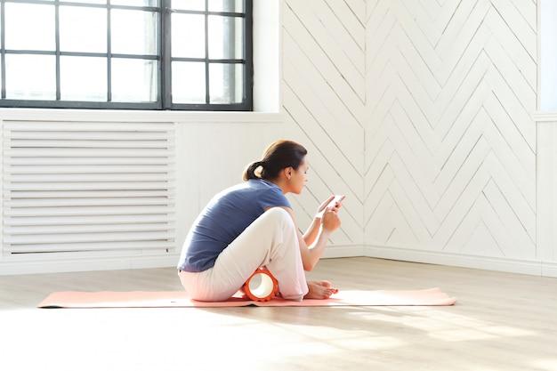 Giovane donna che fa le esercitazioni e che esamina lo smartphone