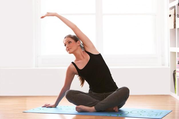 Giovane donna che fa le esercitazioni relative alla ginnastica a casa