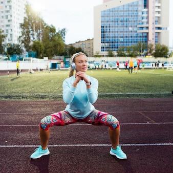 Giovane donna che fa le esercitazioni sullo stadio
