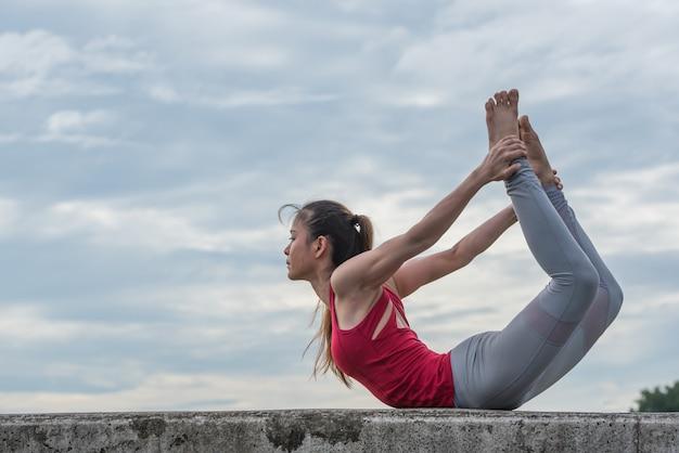 Giovane donna che fa posa di yoga in parco naturale.