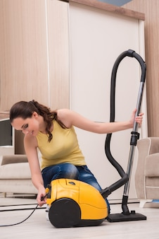 Giovane donna che fa pulizia a casa