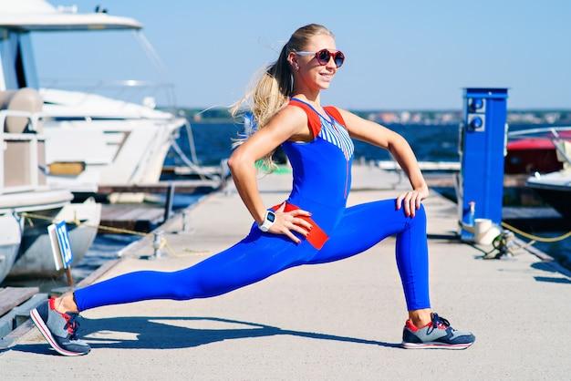 Giovane donna che fa sport al molo