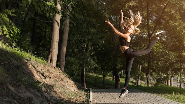Giovane donna che fa sport nel parco