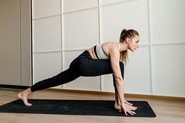 Giovane donna che fa sport sulla stuoia di yoga a casa