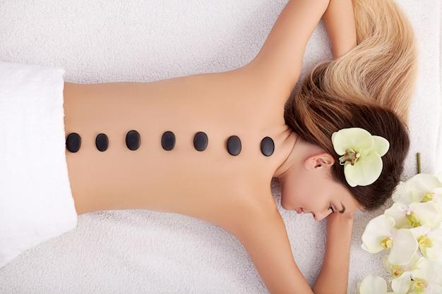 Giovane donna che fa terapia con pietre calde. estetista professionista che massaggia la schiena femminile dalle pietre