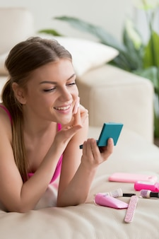 Giovane donna che fa trucco quotidiano semplice a casa
