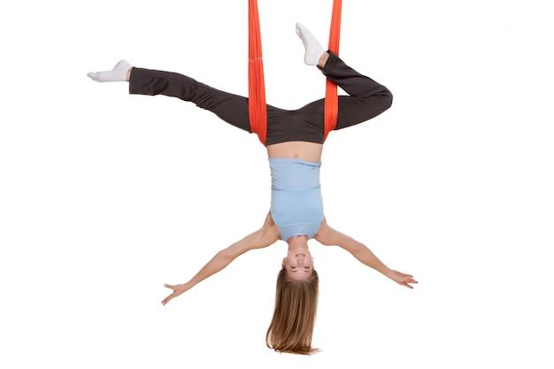 Giovane donna che fa yoga aerea antigravità in amaca sulla parete bianca