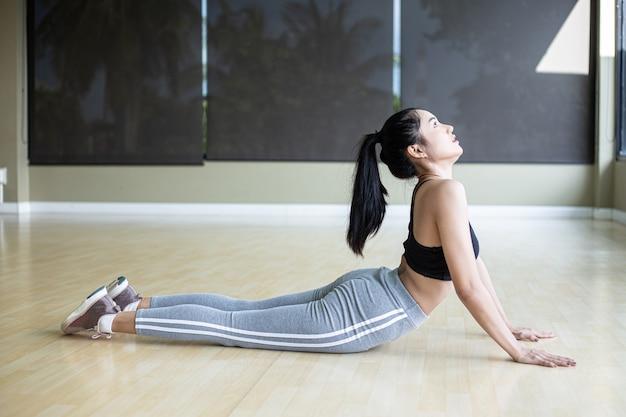 Giovane donna che fa yoga in palestra