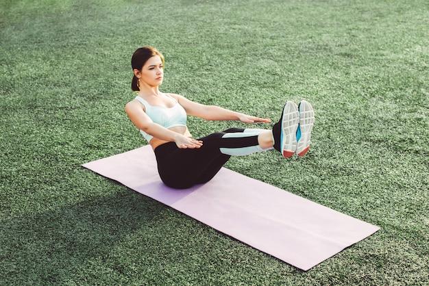 Giovane donna che fa yoga in stadio