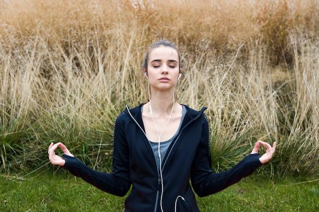 Giovane donna che fa yoga nel parco
